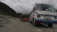 Nepal - August 1, 2015: Buses parked on road next to landslide, boy walks past, slow motion