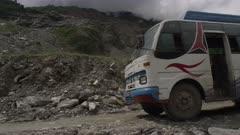 Nepal - August 1, 2015: Bus parked on makeshift road below landslide