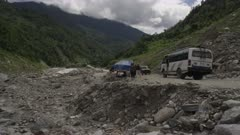Nepal - August 1, 2015: Makeshift road below landslide, people walk, vehicles parked, slow motion