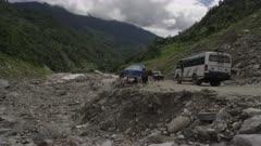 Nepal - August 1, 2015: Makeshift road below landslide, people walk, vehicles parked, slow motion