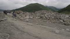 Nepal - August 1, 2015: Motorbike struggles over stones on makeshift road below landslide