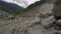 Nepal - August 1, 2015: Green bus drives on makeshift road below landslide