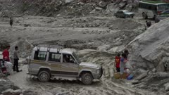 Nepal - August 1, 2015: Vehicle turns on makeshift road, people around