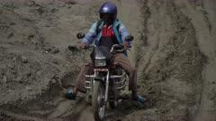 Nepal - August 1, 2015: Man on motorbike on makeshift road below  landslide
