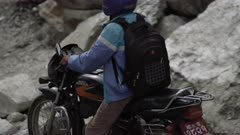 Nepal - August 1, 2015: Slow motion an on motorbike on makeshift road below landslide