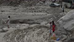 Nepal - August 1, 2015: Women at side of road, vehicle drives on muddy road