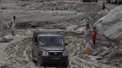 Nepal - August 1, 2015: Vehicle turns on makeshift road, people around