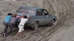 Nepal - August 1, 2015: Slow motion men push blue car on muddy road