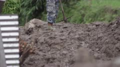 Nepal - August 3, 2015: Soldier in camouflage shorts walks in mud