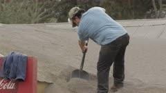 Ensenada, Chile - April 26, 2015: CU man with dust mask shovels volcanic ash off roof