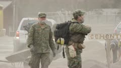 Ensenada, Chile - April 26, 2015: Soldiers wearing dust masks shovel volcanic ash
