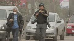 Ensenada, Chile - April 26, 2015: Journalists with face masks, cameras walk along road