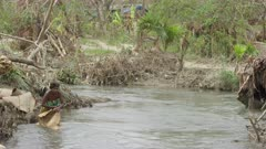 Woman washing a woven mat on the banks of a river after a tropical storm