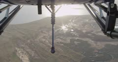 Looking between helicopter skids at the sun glinting on a river, Western Australia