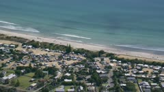 Aerial shot of Waipu Cove township. Zooming in on surfers, Bream Bay, New Zealand