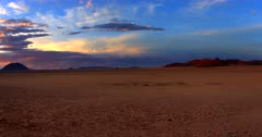 Wide pan across the Garub desert at sunset with stunning lit clouds, the water holes for the wild horses and their well worn paths.