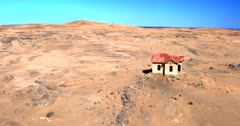 Aerial rotating shot around the abandoned railway station office house at Grasplatz  in the middle of the bare desert.