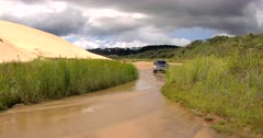 A car, from the front, Crossing the Kauaeparaoa stream at Ninety Mile Beach, New Zealand
