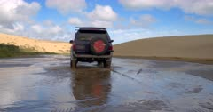 A car, from behind, Crossing the Kauaeparaoa stream at Ninety Mile Beach, New Zealand