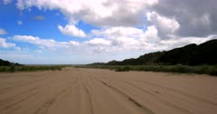 Approaching Ninety Mile beach. Tilt View from the sandy beach to the car wheel spinning