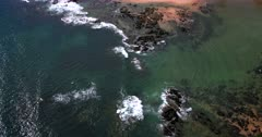 Aerial Tilt shot from the waves crashing on rocks at Cable Bay, New Zealand to the peach colored beach sand