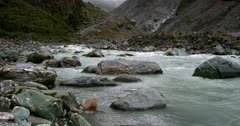 Pan shot down the rapidly flowing glacial river at Fox Glacier