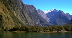 Track shot along the mountains with one snow capped in the distance, at Milford Sound