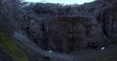 Two waterfalls running down the heavily striated rocks, next to Homer Tunnel