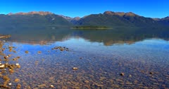 Aerial shot of Lake Te Anau with the mountains reflections on the water covered pebbles.