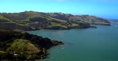 Aerial Tilt shot from the lush green Otago Peninsular hills to the yacht harbour at Port Chalmers.