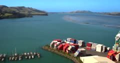 Aerial shot flying over the Port Chalmers cemetery, over the port containers towards the Pacific ocean