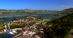 Aerial pan shot across Port Chalmers,Dunedin showing the containers,yachts, ships,harbour and gorgeous surrounding scenery of the Otago Peninsular.