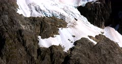 A tilt across a Fiordland hill with snow patches