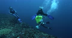 Divers moving the beacon in the ocean over the coral reef and a legde.