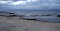 Wide pan shot from the boats and the ocean to the littered a beach at Lembongan.