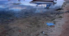 Plastic,Pipes and building materials litter the ocean floor. Which would have been a scenic shot with boats and reflections turns ugly, with pollution.