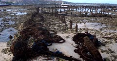 Wide pan shot across the remnants of the sea weed farming. Note the nets,stakes and destroyed coral left behind.