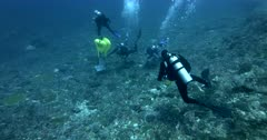 Wide up shot of Scientists holding the concrete block that holds the Acoustic Beacon and moving it to its correct location over the coral reef, with inflated lift bags.