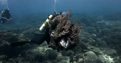 A close up shot of a diver carrying a huge pile of plastic,rubbish  nets and fishing gut,wire out of the sea.