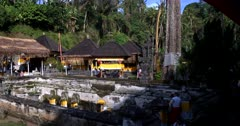 A wide pan shot across the buildings and ancient water works of Goa Gajah, Elephant Cave,Elephant Temple buildings with tourists visiting.