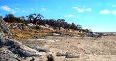 A low Aerial shot along the huge boulders where the Lekubu Baobab trees grow out of rocks.