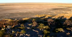 Aerial shot of the Golden hues at sunset  traveling along Lekubu Island with the Makgadikgadi Pan in the surroundings.