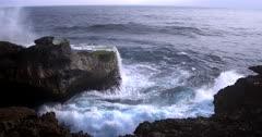 Wide shot of huge waves crashing at Devils pear rugged rocks.
