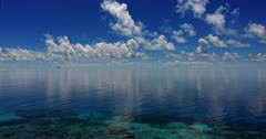 An aerial shot over the calm clear water off Fanamu  Island, with reflections of clouds in Chuuk Lagoon