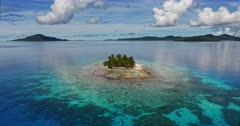 An aerial reveal shot over the gorgeous  Fanamu  Island, on a calm sunny day.