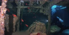 A wide shot of a diver in the hold of the Thistlegorm shipwreck with Soldierfish swimming about.