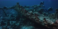 A reveal shot of the Heaven One, Liveaboard shipwreck with divers on the wreck.