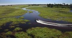 An aerial tracking shot of a boat, cruising through the Okavango Delta River.