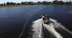 An aerial tracking shot of Tourists on a boat, cruising through the Okavango Delta River.