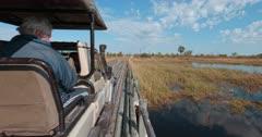 A tracking shot of a safari vehicle driving over a wooden bush bridge.